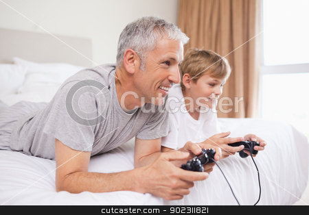 Smiling father and his son playing video games stock photo, Smiling father and his son playing video games in a bedroom by Wavebreak Media