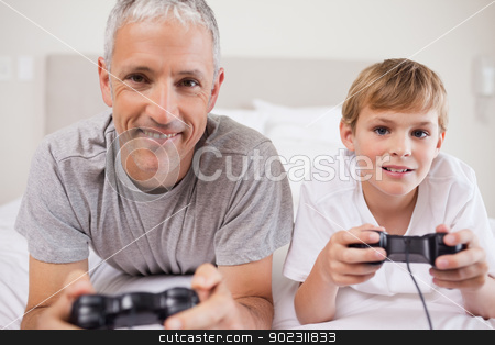 Boy and his father playing video games stock photo, Boy and his father playing video games in a bedroom by Wavebreak Media