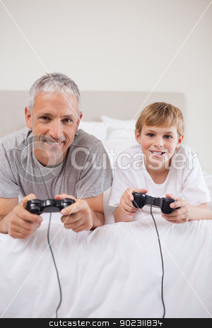 Portrait of a boy and his father playing video games stock photo, Portrait of a boy and his father playing video games in a bedroom by Wavebreak Media