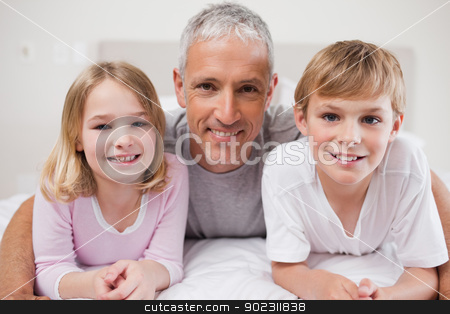 Smiling siblings and their father posing stock photo, Smiling siblings and their father posing in a bedroom by Wavebreak Media