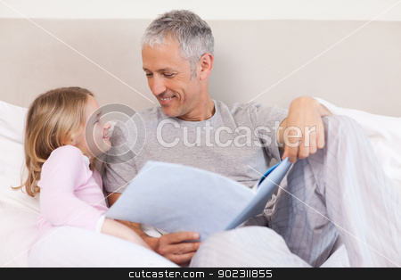 Happy father reading a story to his daughter stock photo, Happy father reading a story to his daughter in a bedroom by Wavebreak Media