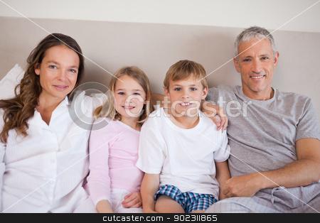 Happy family lying on a bed stock photo, Happy family lying on a bed while looking at the camera by Wavebreak Media