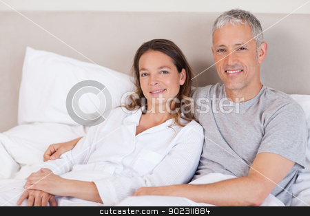 Couple lying on a bed stock photo, Couple lying on a bed in the morning by Wavebreak Media