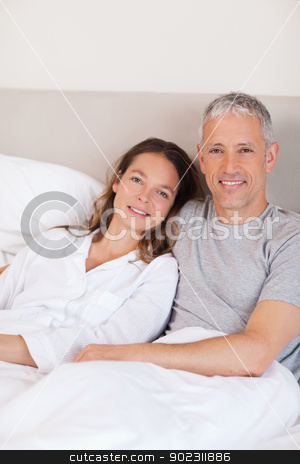 Portrait of a couple lying on a bed stock photo, Portrait of a couple lying on a bed while looking at the camera by Wavebreak Media