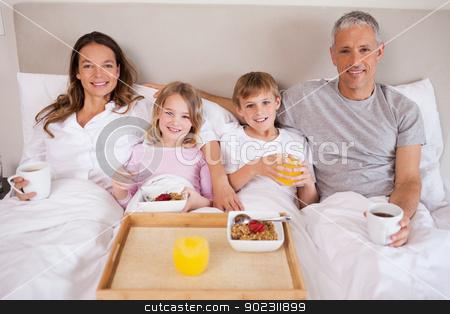 Family having breakfast in a bedroom stock photo, Family having breakfast in a bedroom while looking at the camera by Wavebreak Media