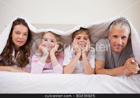 Family lying under a duvet stock photo, Family lying under a duvet in a bedroom by Wavebreak Media