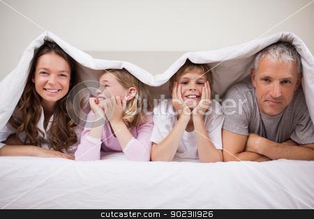 Happy family lying under a duvet stock photo, Happy family lying under a duvet in a bedroom by Wavebreak Media
