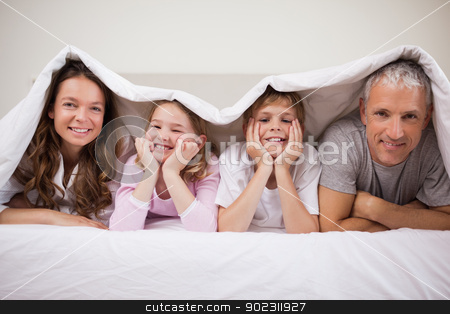 Playful family lying under a duvet stock photo, Playful family lying under a duvet in a bedroom by Wavebreak Media