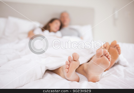 Lovely couple lying in a bed stock photo, Lovely couple lying in a bed with the camera focus on their feed by Wavebreak Media