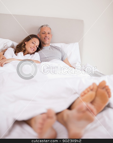 Portrait of a lovely couple lying on their bed stock photo, Portrait of a lovely couple lying on their bed while looking at the camera by Wavebreak Media