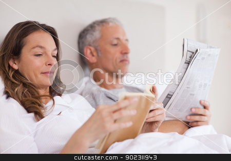 Woman reading a book while her husband is reading the news stock photo, Woman reading a book while her husband is reading the news in their bedroom by Wavebreak Media