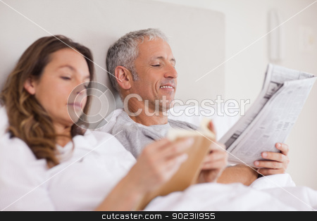 Happy woman reading a book while her husband is reading a newspa stock photo, Happy woman reading a book while her husband is reading a newspaper in their bedroom by Wavebreak Media