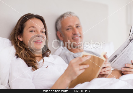 Smiling woman reading a book while her husband is reading the ne stock photo, Smiling woman reading a book while her husband is reading the news in their bedroom by Wavebreak Media