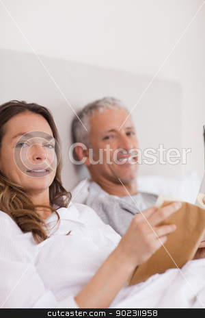 Portrait of a woman reading a book while her husband is reading  stock photo, Portrait of a woman reading a book while her husband is reading the news in their bedroom by Wavebreak Media