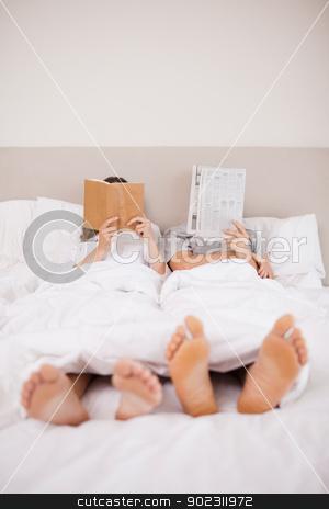 Portrait of playful couple reading stock photo, Portrait of playful couple reading in their bedroom by Wavebreak Media