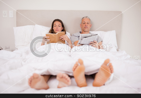Man reading the news while his wife is reading a book stock photo, Man reading the news while his wife is reading a book in their bedroom by Wavebreak Media