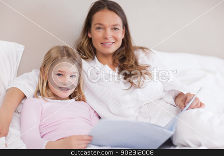 Smiling girl reading a book with her mother stock photo, Smiling girl reading a book with her mother in a bedroom by Wavebreak Media