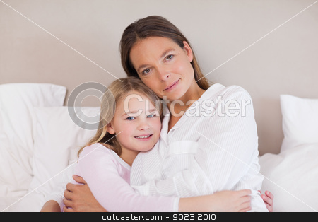 Mother and daughter hugging stock photo, Mother and daughter hugging in a bedroom by Wavebreak Media