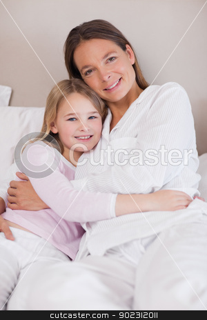 Portrait of a mother and her daughter hugging stock photo, Portrait of a mother and her daughter hugging in a bedroom by Wavebreak Media