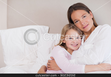 Mother and her daughter hugging stock photo, Mother and her daughter hugging in a bedroom by Wavebreak Media