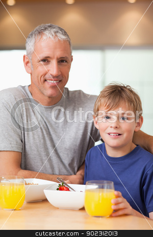 Portrait of a boy and his father having breakfast stock photo, Portrait of a boy and his father having breakfast in a kitchen by Wavebreak Media