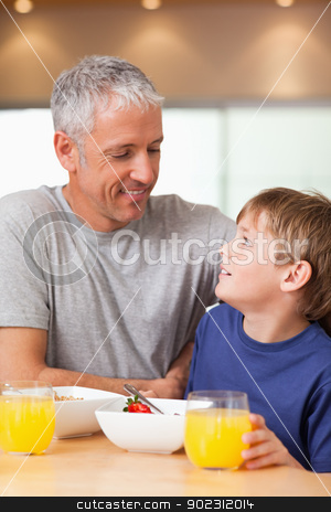 Portrait of a young boy and his father having breakfast stock photo, Portrait of a young boy and his father having breakfast in a kitchen by Wavebreak Media