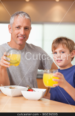 Portrait of a cute boy and his father having breakfast stock photo, Portrait of a cute boy and his father having breakfast in a kitchen by Wavebreak Media