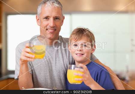 Young boy and his father having breakfast stock photo, Young boy and his father having breakfast in a kitchen by Wavebreak Media