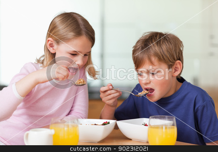 Young children having breakfast stock photo, Young children having breakfast in a kitchen by Wavebreak Media