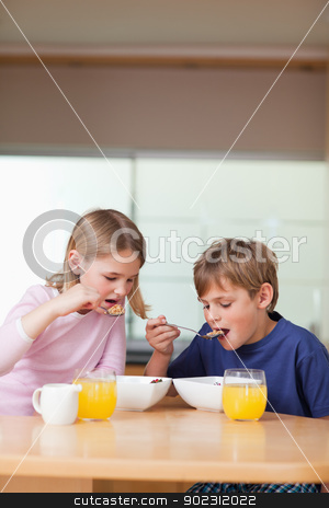 Portrait of children having breakfast stock photo, Portrait of children having breakfast in a kitchen by Wavebreak Media