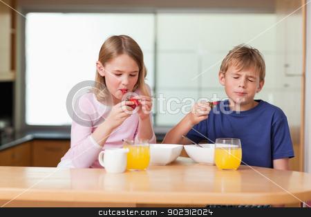 Siblings eating strawberries for breakfast stock photo, Siblings eating strawberries for breakfast in a kitchen by Wavebreak Media