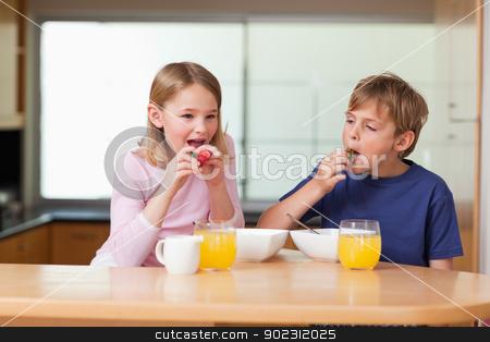 Children eating strawberries for breakfast stock photo, Children eating strawberries for breakfast in a kitchen by Wavebreak Media
