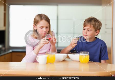 Cute children eating strawberries for breakfast stock photo, Cute children eating strawberries for breakfast in a kitchen by Wavebreak Media