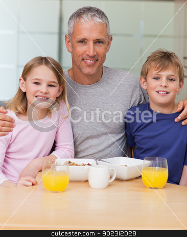 Portrait of a father posing with his children in the morning stock photo, Portrait of a father posing with his children in the morning in a kitchen by Wavebreak Media