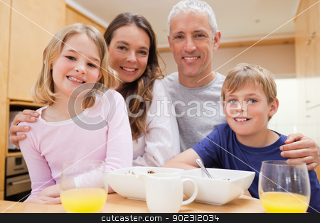 Close up of a smiling family having breakfast stock photo, Close up of a smiling family having breakfast in their kitchen by Wavebreak Media