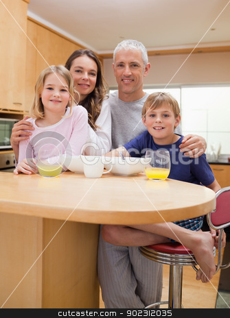 Portrait of a smiling family having breakfast stock photo, Portrait of a smiling family having breakfast in their kitchen by Wavebreak Media