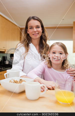 Portrait of a mother and her daughter having breakfast stock photo, Portrait of a mother and her daughter having breakfast in a kitchen by Wavebreak Media