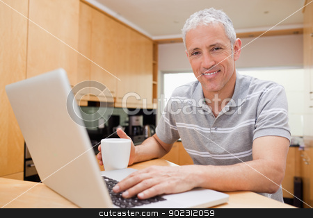 Man using a notebook while drinking tea stock photo, Man using a notebook while drinking tea in a kitchen by Wavebreak Media