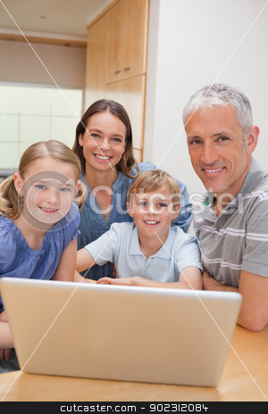 Portrait of a charming family using a laptop stock photo, Portrait of a charming family using a laptop in their kitchen by Wavebreak Media