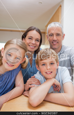 Portrait of a cute family posing in a kitchen stock photo, Portrait of a cute family posing in a kitchen while looking at the camera by Wavebreak Media