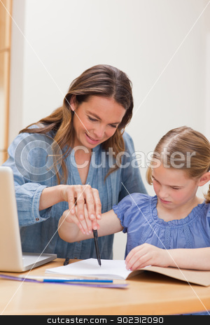 Portrait of a mother helping her daughter doing her homework stock photo, Portrait of a mother helping her daughter doing her homework in a kitchen by Wavebreak Media