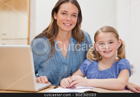 Beautiful woman helping her daughter doing her homework stock photo, Beautiful woman helping her daughter doing her homework in a kitchen by Wavebreak Media