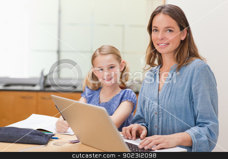 Girl doing her homework while her mother is working with laptop stock photo, Girl doing her homework while her mother is working with laptop in a kitchen by Wavebreak Media