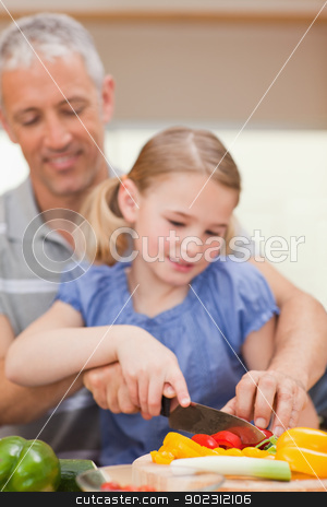 Portrait of a father slicing pepper with his daughter stock photo, Portrait of a father slicing pepper with his daughter in a kitchen by Wavebreak Media