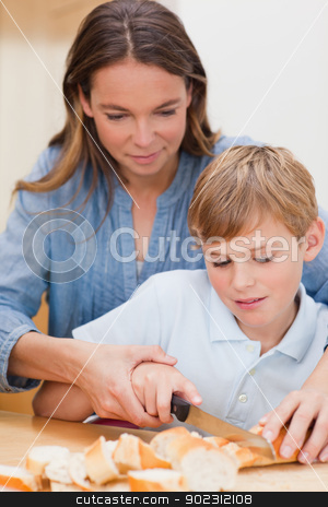 Portrait of a woman slicing bread with her son stock photo, Portrait of a woman slicing bread with her son in a kitchen by Wavebreak Media