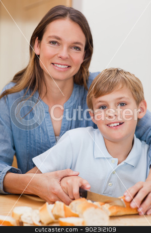 Portrait of a mother slicing bread with her son stock photo, Portrait of a mother slicing bread with her son in a kitchen by Wavebreak Media