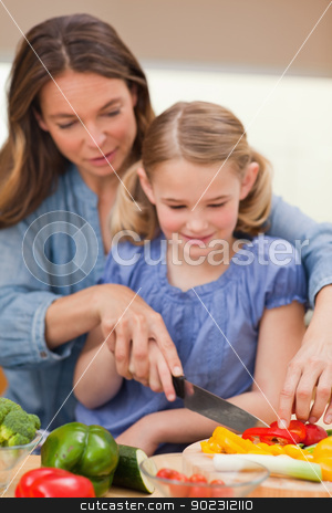 Portrait of a mother slicing pepper with her daughter stock photo, Portrait of a mother slicing pepper with her daughter in a kitchen by Wavebreak Media