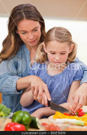 Portrait of a woman slicing pepper with her daughter stock photo, Portrait of a woman slicing pepper with her daughter in a kitchen by Wavebreak Media