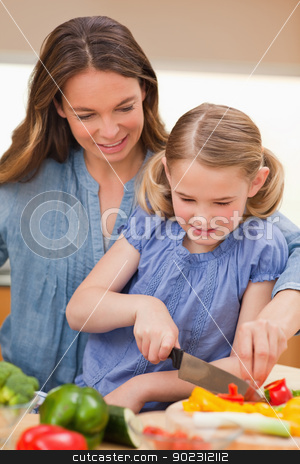 Portrait of a mother slicing bell pepper with her daughter stock photo, Portrait of a mother slicing bell pepper with her daughter in a kitchen by Wavebreak Media