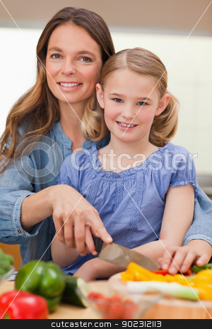 Portrait of a woman slicing bell pepper with her daughter stock photo, Portrait of a woman slicing bell pepper with her daughter in a kitchen by Wavebreak Media